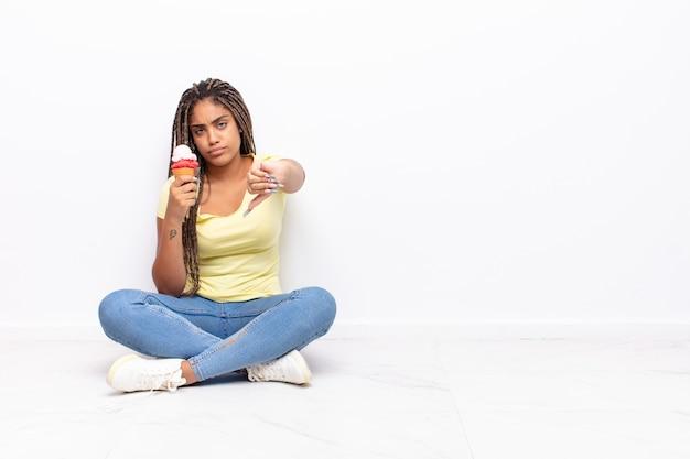 クロス、怒り、イライラ、失望、または不満を感じ、真剣な表情で親指を下に向けている若いアフロ女性。アイスクリームのコンセプト