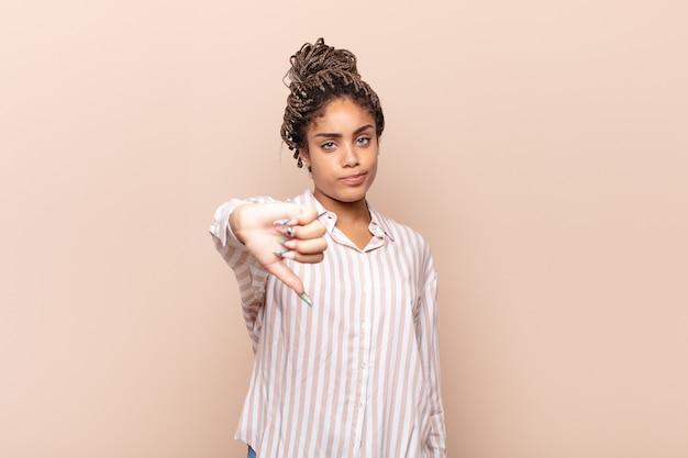 Молодая афро-женщина чувствует себя сердитой, сердитой, раздраженной, разочарованной или недовольной, показывает палец вниз с серьезным взглядом