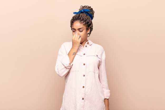 Young afro woman feeling disgusted, holding nose to avoid smelling a foul and unpleasant stench