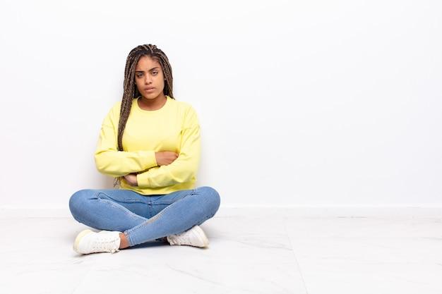 不満と失望を感じ、深刻に見え、イライラし、腕を組んで怒っている若いアフロ女性