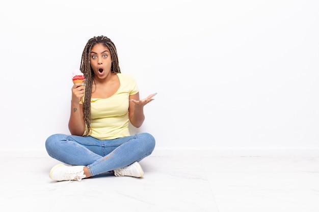 若いアフロの女性は、ストレスと恐怖の表情で、非常にショックを受け、驚き、不安とパニックを感じています。アイスクリームのコンセプト