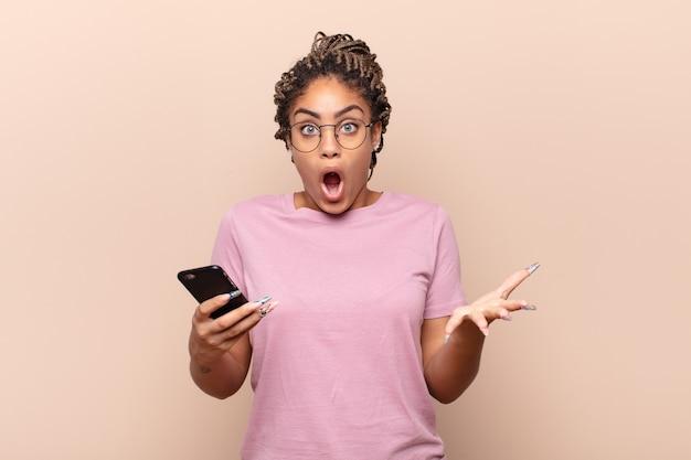 若いアフロの女性は、ストレスと恐怖の表情で、非常にショックを受け、驚き、不安とパニックを感じています。スマートフォンのコンセプト