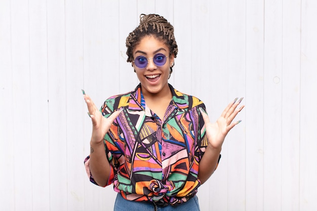 Молодая афро-женщина чувствует себя счастливой, взволнованной, удивленной или шокированной, улыбается и удивляется чему-то невероятному