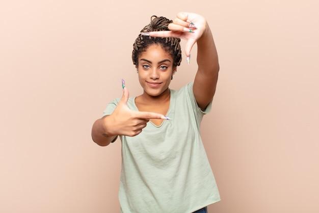幸せで、友好的で、前向きで、笑顔で、手でポートレートやフォトフレームを作る若いアフロ女性