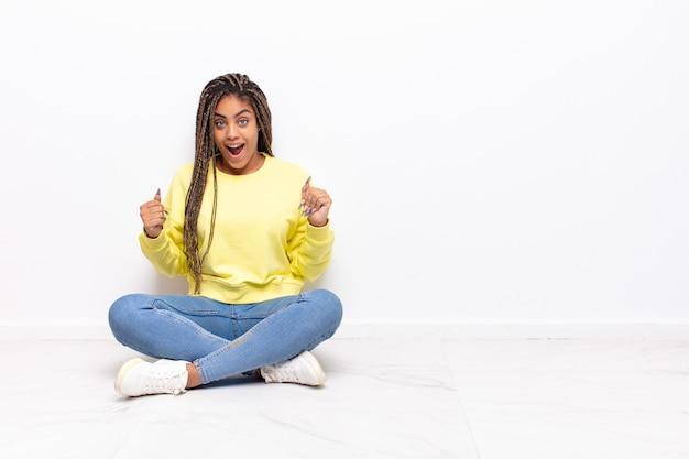 Молодая афро-женщина чувствует себя счастливой, позитивной и успешной, празднует победу, достижения или удачу