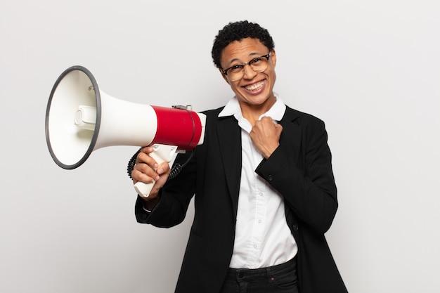 Молодая афро-женщина чувствует себя счастливой, позитивной и успешной, мотивированной, когда сталкивается с проблемой или празднует хорошие результаты