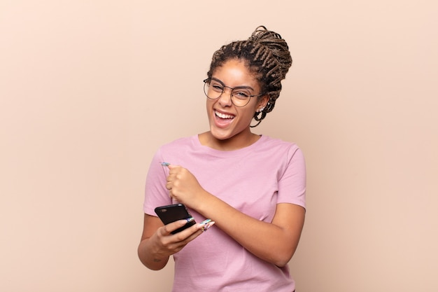 Young afro woman feeling happy, positive and successful, motivated when facing a challenge or celebrating good results. smart phone concept
