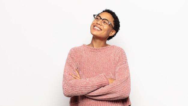 幸せ、誇り、希望を感じ、不思議に思ったり考えたり、腕を組んでスペースをコピーするために見上げる若いアフロ女性