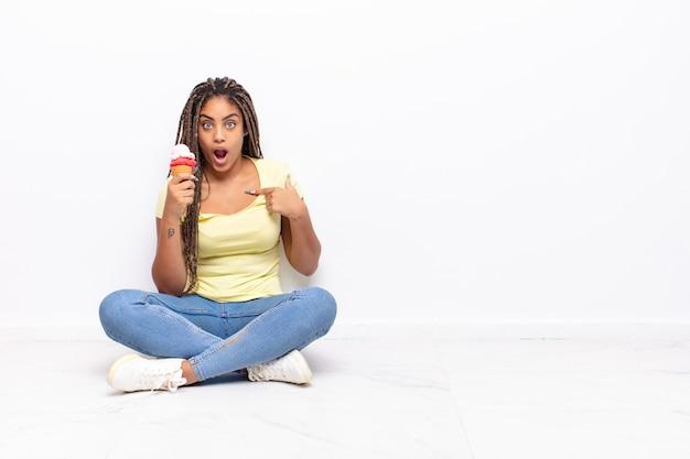 幸せ、驚き、誇りを感じ、興奮した驚きの表情で自分を指差す若いアフロ女性。アイスクリームのコンセプト