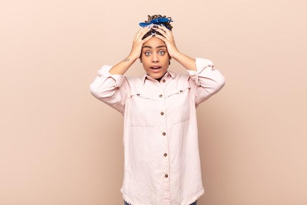 젊은 아프리카 여성은 소름 끼치고 충격을 받고 손을 머리에 들고 실수에 당황합니다.