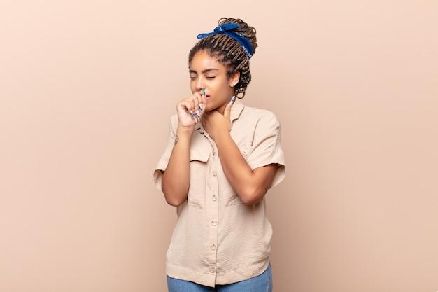 喉の痛みとインフルエンザの症状が分離されて気分が悪い若いアフロ女性