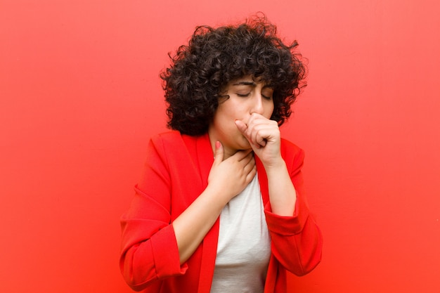Young afro woman feeling ill with a sore throat and flu symptoms, coughing with mouth covered