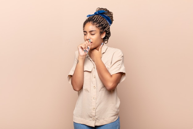 Young afro woman feeling ill with a sore throat and flu symptoms isolated