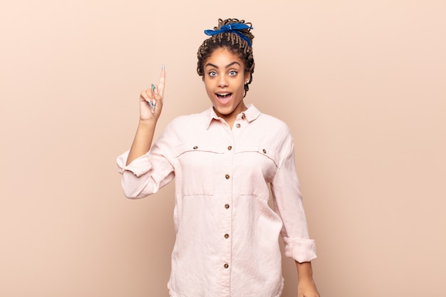 アイデアを実現した後、幸せと興奮の天才のように感じる若いアフロの女性、元気に指を上げて、エウレカ!