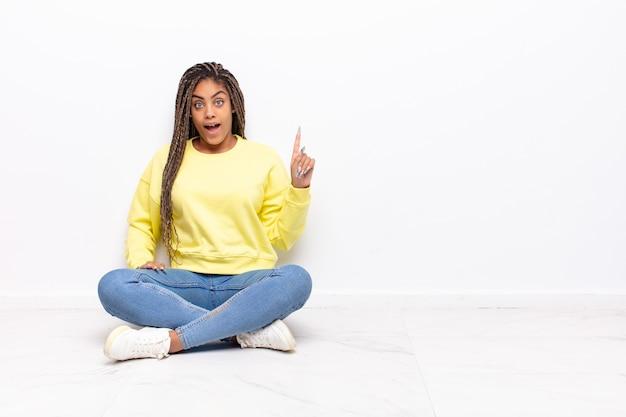 アイデアを実現した後、幸せで興奮した天才のように感じる若いアフロ女性、元気に指を上げる、エウレカ!