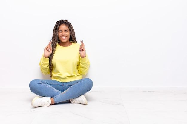 Молодая афро-женщина нервничает и полна надежд, скрещивает пальцы, молится и надеется на удачу