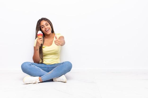 誇りに思って、のんきで、自信を持って幸せに感じ、親指を立てて前向きに笑っている若いアフロ女性