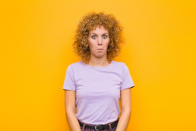 Young afro woman feeling sad and stressed, upset because of a bad surprise, with a negative, anxious look against orange wall