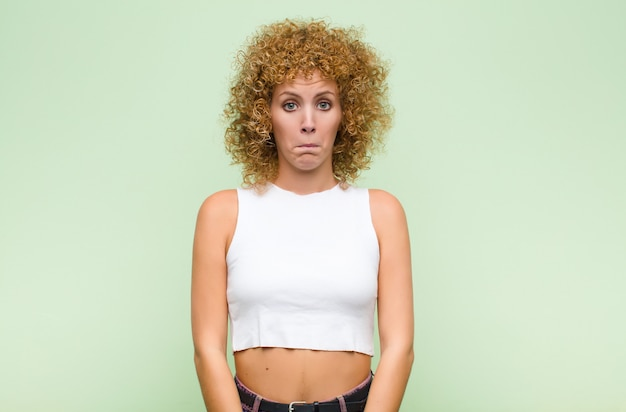Young afro woman feeling sad and stressed, upset because of a bad surprise, with a negative, anxious look over green wall
