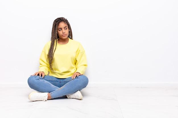 悲しみ、動揺、または怒りを感じ、否定的な態度で横を向いて、意見の相違に眉をひそめている若いアフロ女性