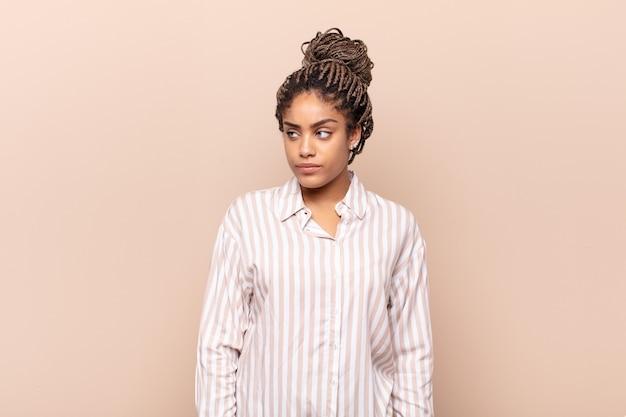 Молодая афро-женщина грустит, расстроена или злится и смотрит в сторону с негативным отношением, хмурясь в знак несогласия