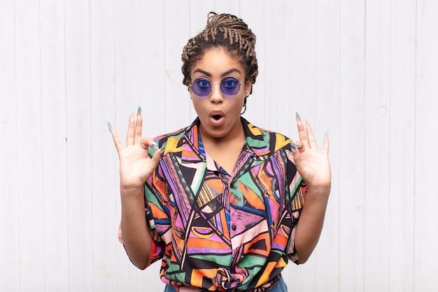ショックを受け、驚き、驚きを感じ、両手で大丈夫なサインをする承認を示している若いアフロ女性