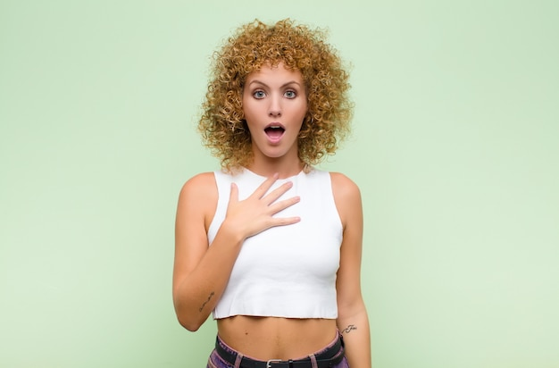 Young afro woman feeling shocked, astonished and surprised, with hand on chest and open mouth, saying who, me? against green wall