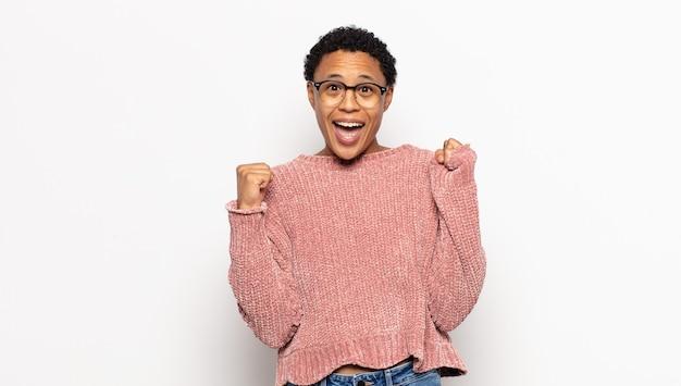젊은 아프리카 여성은 충격을 받고 흥분하고 행복하며 웃고 성공을 축하하며 와우라고 말합니다!