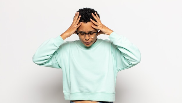 ストレスと欲求不満を感じ、手を頭に上げ、倦怠感、不幸、片頭痛を感じる若いアフロ女性