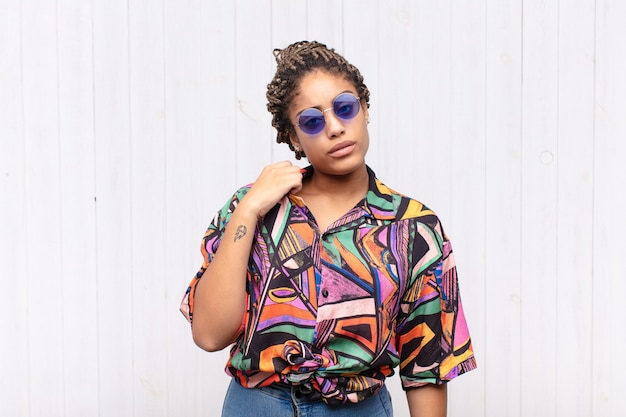 若いアフロ女性は、ストレス、不安、疲れ、欲求不満を感じ、シャツの首を引っ張って、問題で欲求不満に見えます