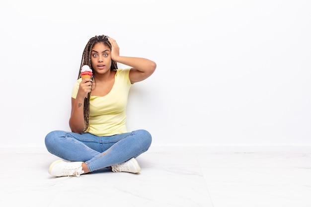 若いアフロの女性は、ストレス、心配、不安、または恐怖を感じ、頭に手を置いて、誤ってパニックに陥っています。アイスクリームのコンセプト