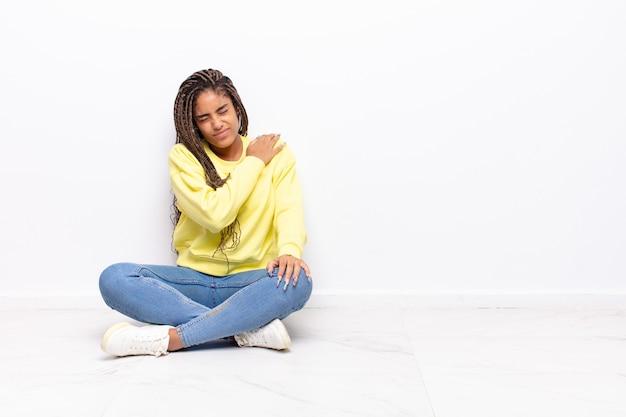 疲れ、ストレス、不安、欲求不満、落ち込んでいる、背中や首の痛みに苦しんでいる若いアフロ女性