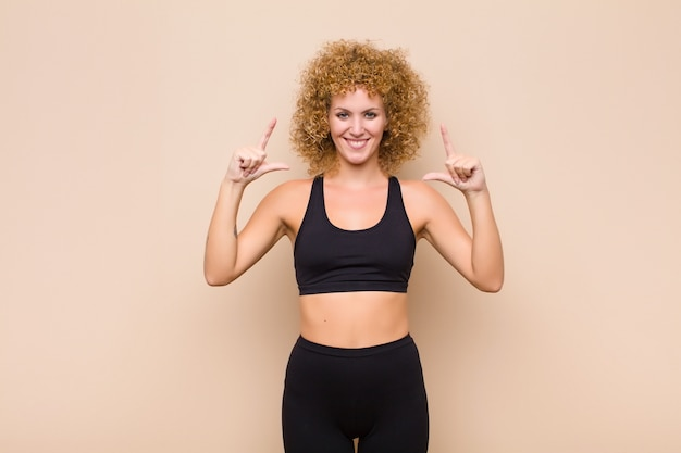Young afro woman framing with both hands, looking positive and happy