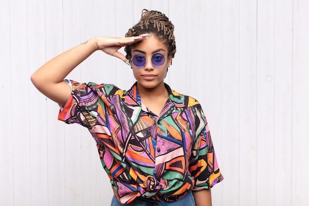 Молодая афро-женщина приветствует камеру военным салютом в знак чести и патриотизма, проявляя уважение