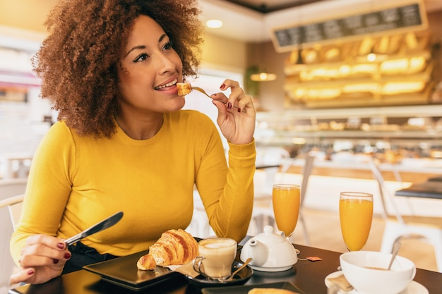 Young afro woman having a breakfast, eating a croissant and drinking a coffee and an orange juice.