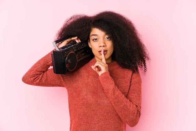 秘密を保持または沈黙を求めて分離されたカセットを保持している若いアフロ女性。