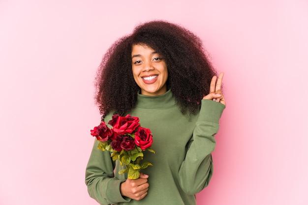 分離されたバラを保持している若いアフロ女性指でrosesshowing番号2を保持している若いアフロ女性