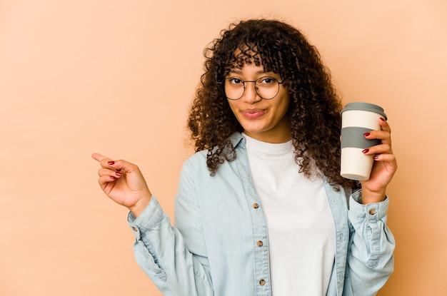 持ち帰り用のコーヒーを持って笑顔で脇を向いて、空白のスペースで何かを見せている若いアフロ女性