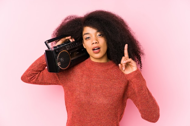 Young afro woman holding a cassete isolated having an idea, inspiration concept.