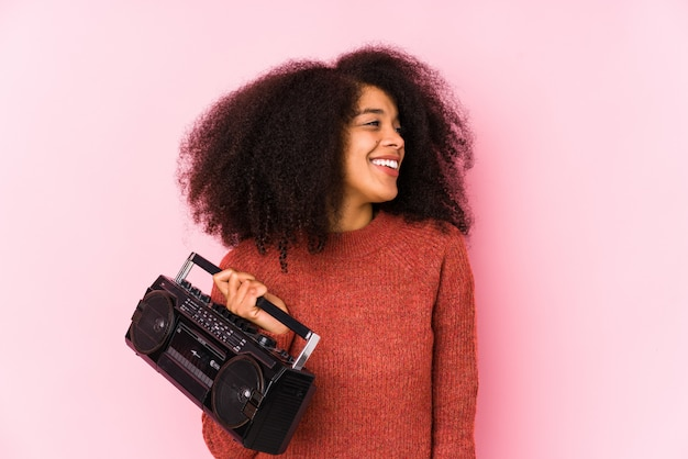 Young afro woman holding a cassete isolated looks aside smiling, cheerful and pleasant.