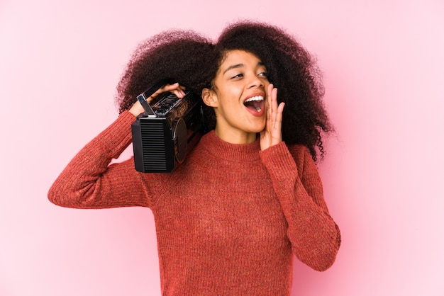 Young afro woman holding a cassete isolated shouting and holding palm near opened mouth.