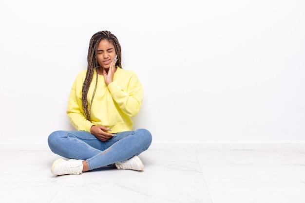Молодая афро-женщина, держащая щеку и страдающая от болезненной зубной боли, чувствует себя больной, несчастной и несчастной, ищет стоматолога