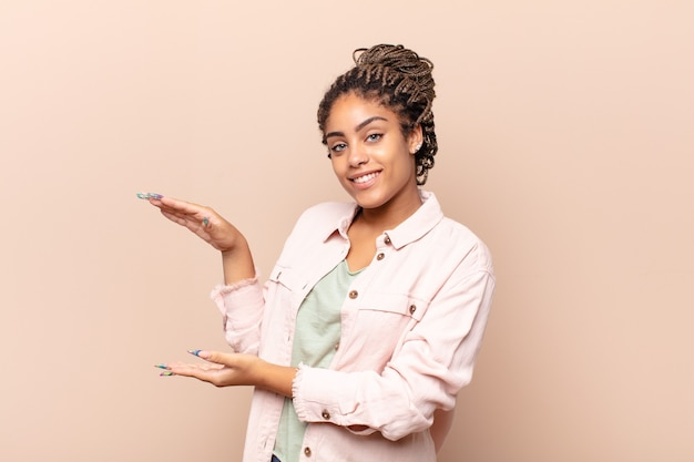 Young afro woman holding an object with both hands isolated