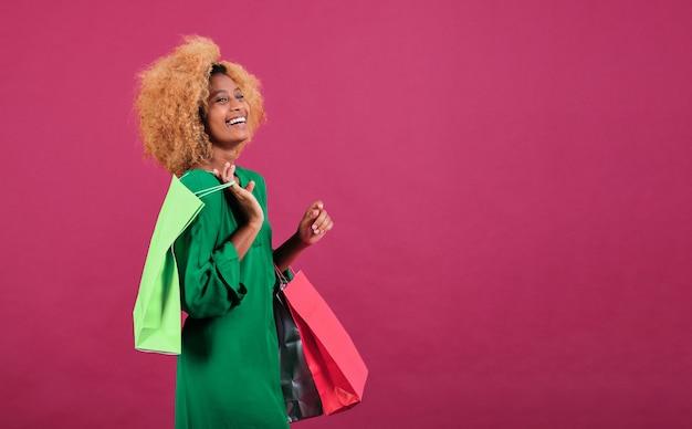Молодая афро женщина держит хозяйственные сумки, стоя на изолированном фоне. концепция продажи сезона черная пятница.