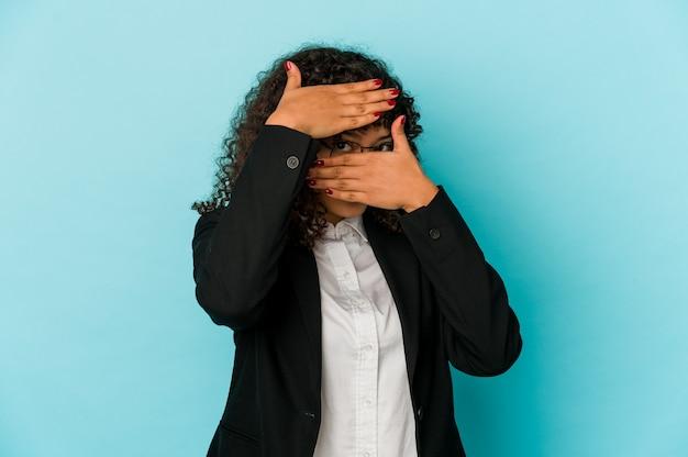 Молодая афро-женщина изолированно моргает пальцами в камеру, смущенно закрывая лицо
