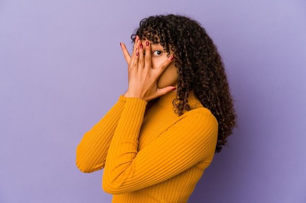 Young afro woman isolated blink through fingers frightened and nervous
