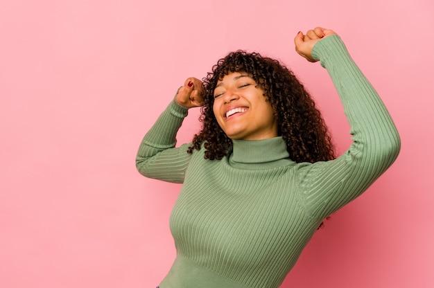 特別な日を祝って孤立した若いアフロ女性は、エネルギーでジャンプして腕を上げる