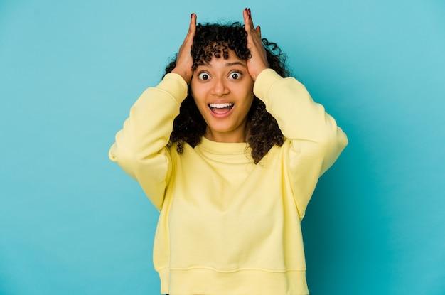 若いアフロ女性は叫び、非常に興奮し、情熱的で、何かに満足している