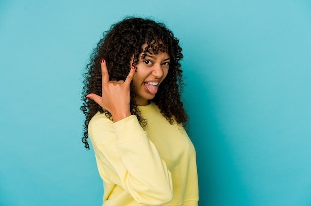 指でロックジェスチャーを示す孤立した若いアフロ女性