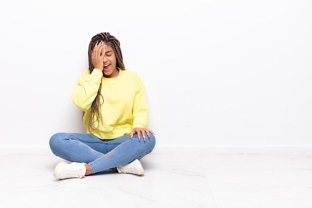 Молодая афро-женщина смеется и хлопает себя по лбу, как будто говоря «ох!» я забыл или это была глупая ошибка